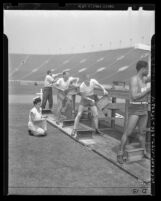 Four male Los Angeles police applicants being evaluated during physical fitness tests in 1946