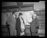 Astrologer Mrs. Colby Griffin examining horoscope with her attorney Robert A. Neeb and friend Ernest Wyher