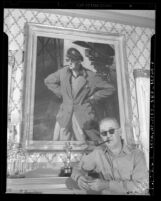 Director John Ford standing before portrait of himself and Academy Award statue, circa 1946