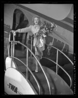 Actress Marlene Dietrich exiting airplane in Los Angeles, Calif. after entertaining troops during World War II