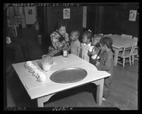 African American woman feeding cod liver oil to four African American children at a Macy Street school, Los Angeles, circa 1938