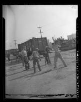 Cole Brothers Circus workers pounding in stakes for tent in Los Angeles, Calif.