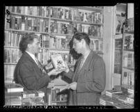 "Reporter Vern Partlow and Joseph Epstein looking at ""Canterbury Tales"" book, deemed obscene, circa 1946"