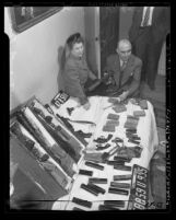 Loren Roosevelt and police lieutenant Earle Rambeau with arsenal of weapons found in suspected murderer's apartment, Los Angeles, Calif., 1946