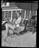 "Dorothy McGrath lounging on a Los Angeles beach while using ""Walkie Talkie"" radio set, circa 1947"
