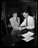 Frank Sinatra being fingerprinted by police officer Robert Rogers for gun permit in Los Angeles, Calif., 1947
