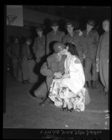 California National Guard signal corpsmen look on as corpsman kisses his wife good-bye, 1950