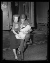 California National Guardsmen Dan Steelman seated in doorway of train with his wife and baby son, 1950