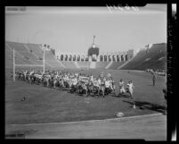 Western State Conference college football players running across Los Angeles Coliseum field, 1950