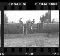 Mexican children hanging around fence along United States-Mexico border in Calexico, Calif., 1979