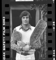 Curtis Creath of UCLA's Beta Theta Pi fraternity, holding pledge paddles, 1979
