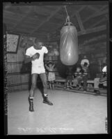 Boxer Ike Williams punching bag as children look on during training at Soper's Ranch, Calif., 1948