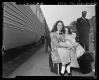 11 year-old actress Margaret O'Brien seated on suitcase holding a doll at Los Angeles Union Station, 1948