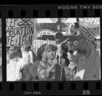 "Women holding large crucifix amid protesters with ""Keep Abortion Legal"" signs, Los Angeles, Calif., 1989"