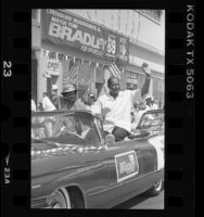 Tom Bradley and Marla Gibbs passing his Crenshaw campaign headquarters during parade in Los Angeles, Calif., 1989