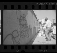 City councilman, Nate Holden helping to paint over graffiti covered wall in Los Angeles, Calif., 1989