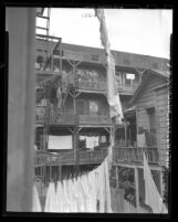 Housing Director Holtzendorff and men going up rickety fire escape of tenement during tour of slum areas in Los Angeles, Calif., 1948