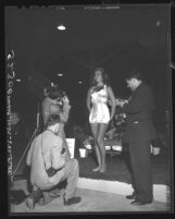 Three amateur photographers surrounding model at Los Angeles Photo Fair, 1948