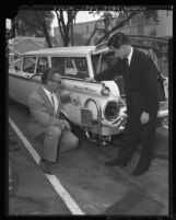 Richard D. Hopa and Hiroshi Kimura demonstrating anti-smog device for automobiles in Los Angeles, Calif., 1960