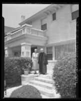 Dr. and Mrs. Elmer Ellsworth Helms standing on the porch of the home given to them by First Methodist Church in Los Angeles, Calif., 1948