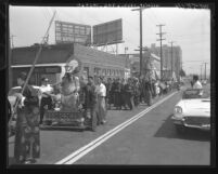 Procession for warrior Kwong Kong statue traveling down Broadway Street in Los Angeles, Calif., 1960