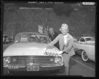 Actress Ginger Rogers pastes Nixon-Lodge sticker on automobile as she talks to actor Cesar Romero, Calif., 1960