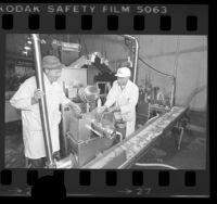 Irving Geldin and Harry Segal watching mechanical meat deboning machine at Geldin Meats in Vernon, Calif., 1976