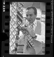 Rudy Cervantes inspecting Mickey Mouse ties in Los Angeles, Calif., 1976
