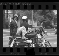Clown getting a ride from a motorcycle policeman in Los Angeles, Calif., 1976