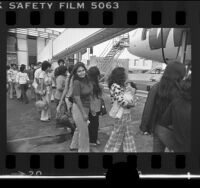 Undocumented immigrants boarding airplane in Los Angeles for deportation to Mexico City, 1976