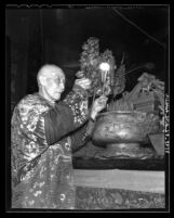 Woo Tong making offering in ceremony at the Chinese Temple of Kuan Kung, Los Angeles, 1935