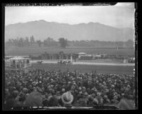 View from grand stands of crowd watching close finish at Santa Anita racetrack with mountains in background, Arcadia, 1935
