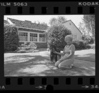Maurice Rachman and dog out front of her home that's used in TV ads and films, Studio City, Calif., 1976