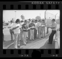 Rapid Transit District Division Manager Jack Greasby handing out letters to picketing drivers in El Monte, Calif., 1976
