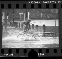 Boy riding bicycle through flooded street in Playa del Rey, Los Angeles, 1976