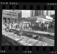 Crowd dashing to tables laden with books at Los Angeles Public Library's book sale, 1976