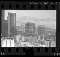 Cityscape with snow covered mountains of downtown Los Angeles, 1977