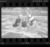 Jack McKee and Rev. Kenn Gulliksen baptizing Diane Hunter in surf at Will Rogers State Beach, Calif., 1976