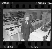 William R. Hoover, president of Computer Sciences Corp. standing amongst rows of computer data banks, Calif., 1977
