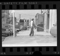 Man hosing down sidewalk on Towne Avenue in violation of water conservation ordinance in Los Angeles, Calif., 1977