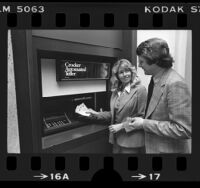 Couple demonstrating a Crocker Bank Automated Teller machine (ATM), Calif., 1977