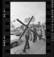 Reverend Arthur Blessitt walking along the Sunset Strip at Larrabee St. with his wheeled cross, Calif., 1977