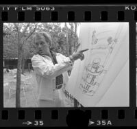 Evel Knievel showing diagram of his drop from airplane stunt, 1977