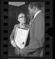 Tom Bradley presenting diploma to comedian George Burns in Los Angeles, Calif., 1977