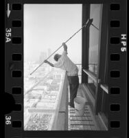Window washer Vince Schaefer working on skyscraper in Los Angeles, Calif., 1977