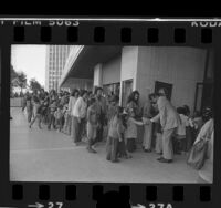 "Mayor Tom Bradley greeting underprivileged children at screening of film, ""Pete's Dragon,"" at Century City, Calif., 1977"