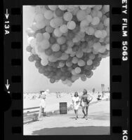 "Nonprofit group handing out balloons printed with ""The Process…"" at Santa Monica Beach, Calif., 1979"