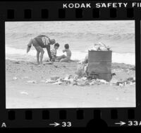Lifeguard picking up litter on trash strewed beach in Los Angeles, Calif., 1979
