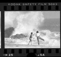 Two youngsters watching waves crash against rocks at Point Mugu State Park, Calif., 1979