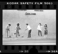 Koreatown residents sweeping sidewalks outside Shin Jung restaurant in Los Angeles, Calif., 1979